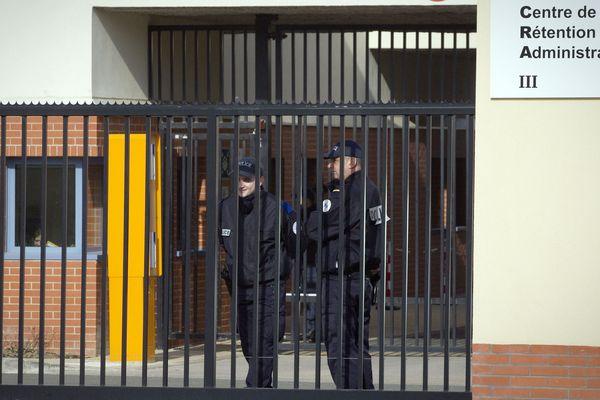 Des policiers derrière l'entrée du Centre de Rétention Administrative (CRA) du Mesnil-Amelot (Seine-et-Marne).