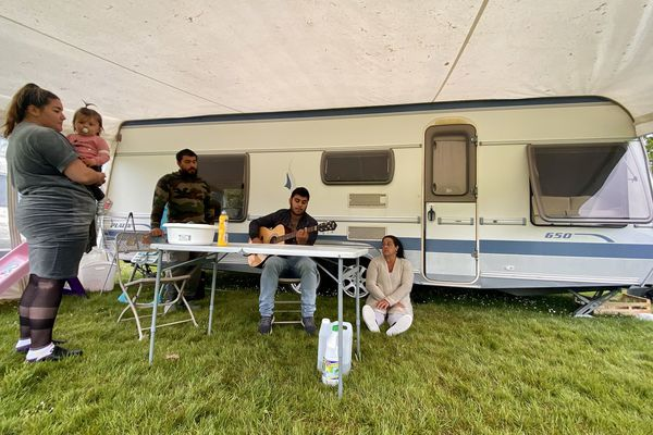 Une famille installée sur le terrain de foot d'Availles-Limouzine se réunit pour chanter.