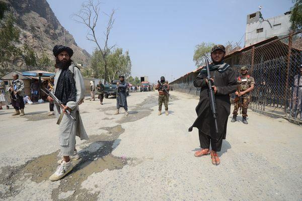 Un soldat paramilitaire pakistanais, à gauche, et des combattants talibans montent la garde de leurs côtés respectifs, à un point de passage frontalier entre le Pakistan et l'Afghanistan, à Torkham, dans le district de Khyber.