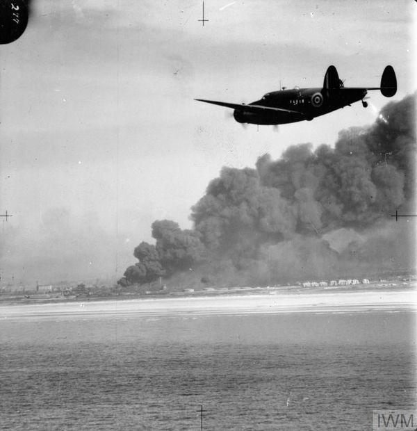 Un avion de reconnaissance britannique Lockheed Hudson s'approche de Dunkerque en flammes en mai 1940.