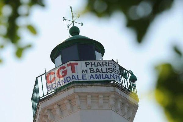 """La CGT """" Phares et balises """" a accroché une banderole sur le phare du quai Vallin pour dénoncer le scandale de l'amiante. C'était à La Rochelle, le 24 07 2014."""