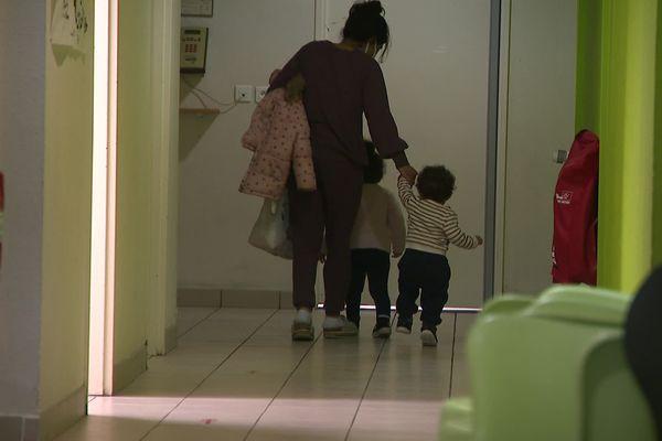 Une femme et ses enfants dans un couloir du foyer d'accueil de l'APAFED à Cenon.