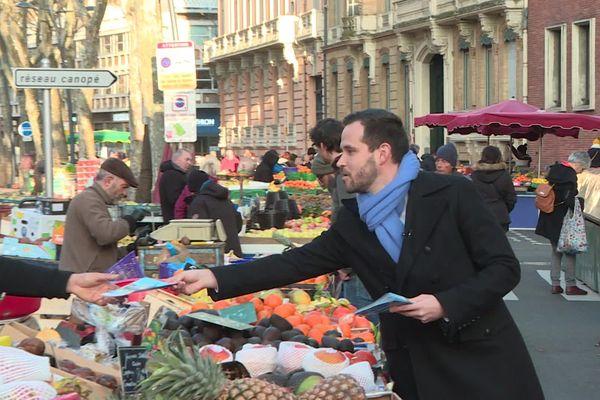 Quentin Lamotte, candidat à la mairie de Toulouse avec la liste Rassemblement Toulousain, distribue des tracts sur le marché du Cristal.