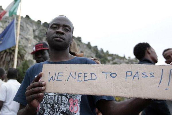 """A la frontière franco-italienne en juin dernier. Sur le carton: """"nous devons passer !"""""""