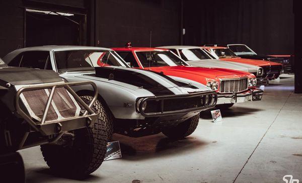"""Du premier à l'arrière plan : la Fast Attack Vehicle de """"Fast & Furious 7""""; l'Offroad Camaro de """"Fast & Furious 7""""; la Gran Torino de """"Starsky & Hutch"""", la Chevelle de """"Drive"""", la Dodge Charger de """"General Lee"""" et Ford LTD de """"Men In Black"""""""