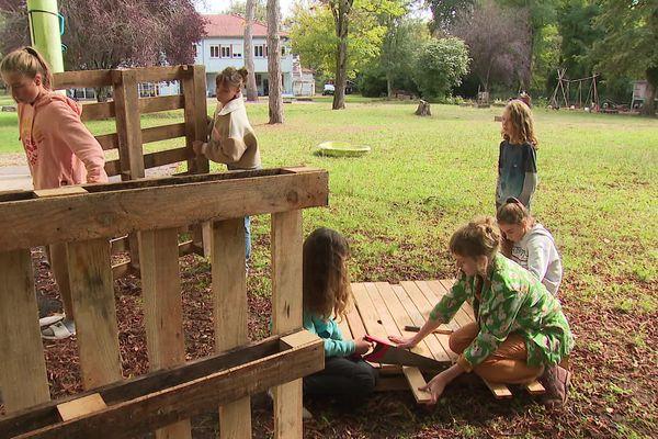 Entre deux cours, les élèves construisent une structure pour les chèvres de l'établissement.