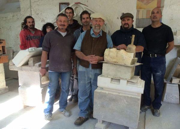 Claude, avec béret, Christophe, avec casquette, et leurs stagiaires, dans l'atelier.