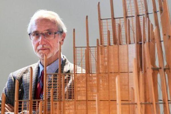 L'architecte Renzo Pizno pose à côté d'une maquette du centre culturel Tjibaou de Nouméa, le 10 novembre 2015 à Paris