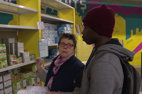Anne Pouliquen, bénévole aux Restos du coeur de Mulhouse, en train de remplir le panier de Boubacar, étudiant en informatique précaire.