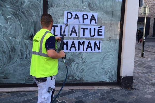 """Un employé de la ville de Besançon efface une affiche posée par le collectif """"Collage féminicides"""", le 16 septembre 2019."""