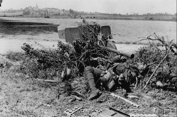Dépouille d'un soldat français du 4e régiment de Dragons Montés à côté d'un canon antichar, aux abords du Mont-Saint-Eloi.