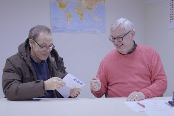 Pierre (à droite) prend avec patience et humour les documents qu'Abdelhahafid lui apporte.