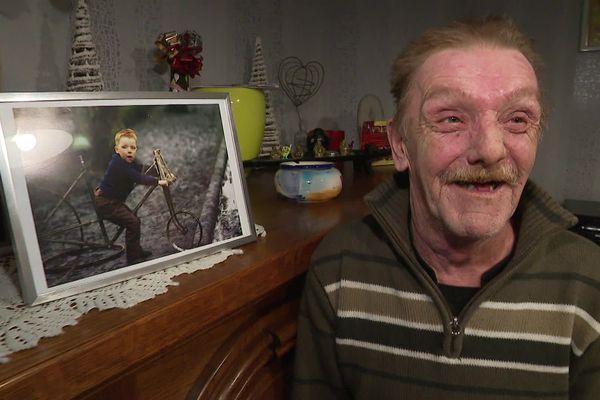 Jean-Michel Longeois pose à côté de ses photos encadrées