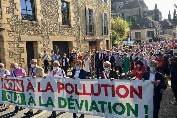 """Le cortège des pro-déviation a défilé dans le bourg de Beynac avec des fourches en bois et derrière une banderole """"Non à la pollution, oui à la déviation"""", dimanche 13 septembre."""