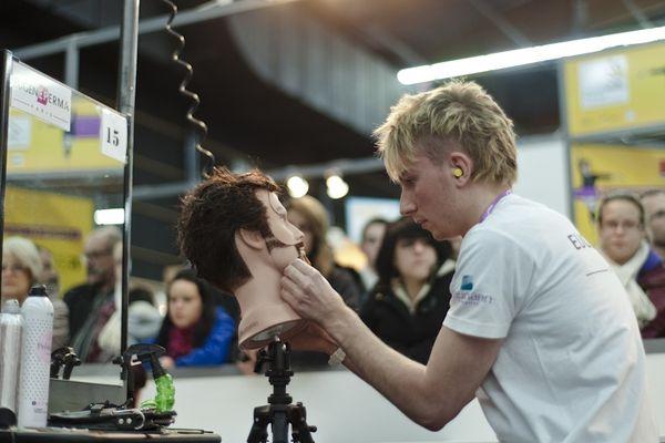 """C'est le dernier salon où l'on cause! Les abords du stand """"coiffure"""" ne désemplissent pas depuis l'ouverture des 42ème Olympiades des Métiers à Clermont-Ferrand. Il faut jouer des coudes pour admirer le travail des artistes."""