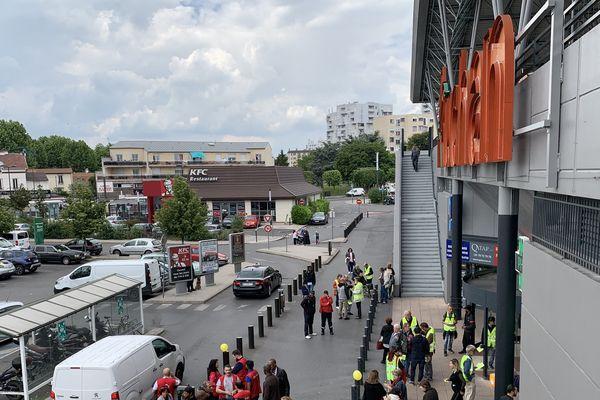 Des salariés de l'hypermarché Auchan de Villetaneuse, accompagnés par des gilets jaunes, tous postés devant le centre commercial.