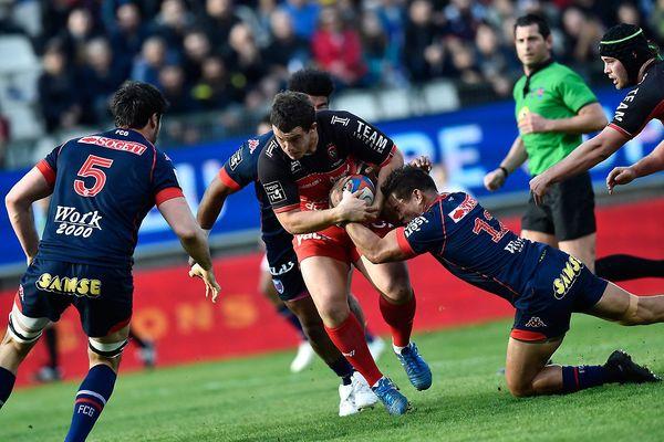Le talonneur français Anthony Etrillard de Toulon est attaqué par le centre néo-zélandais de Grenoble Nigel Hunt lors du match de rugby à XV du FC Grenoble (FCG) et du RC Grenoble (RCT) le 19 mars 2016 au stade Alpes à Grenoble.