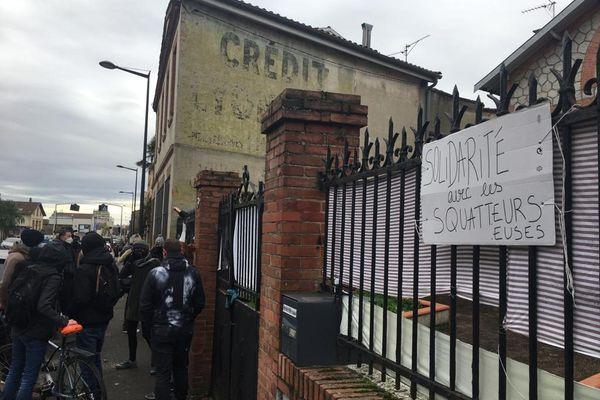 Sur le trottoir des personnes venues déloger les squatteurs. Derrière la grille, les défenseurs des occupants de la maison.