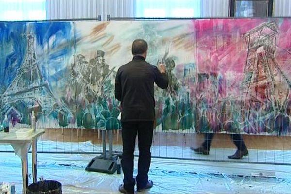 L'artiste Corado Boust, devant la fresque qu'il a réalisé durant cette journée de solidarité à Montceau-les-Mines