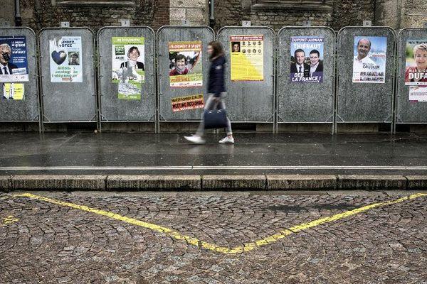 Une passante longe les panneaux d'affichage des candidats aux régionales à Dijon. Photo d'illustration.