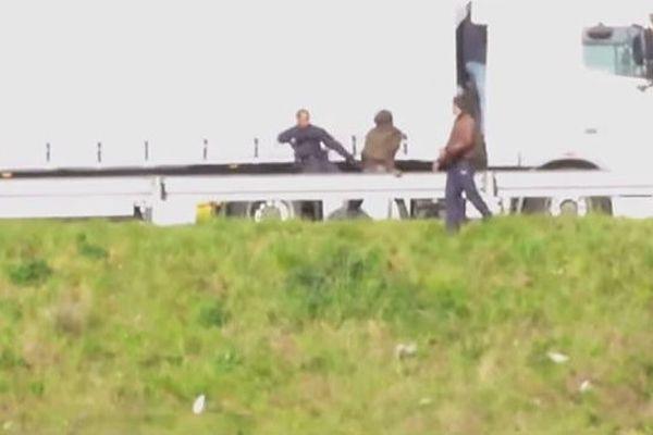 Le CRS, filmé en train de donner un coup de pied à un migrant, pour l'éloigner d'un poids lourd.