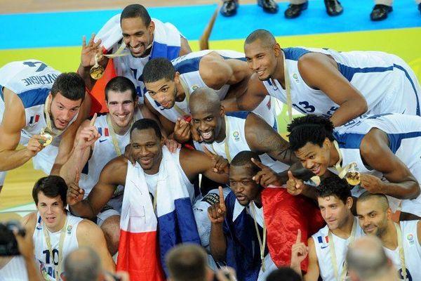 Joffrey Lauvergne (à gauche) montre fièrement sa médaille d'or remportée avec l'équipe de France de basket lors de l'Eurobasket 2013, le 22 septembre 2013, à Ljubljana (Slovénie)