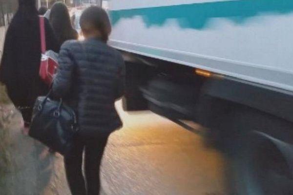 Les jeunes collégiens longent la voie de circulation très fréquentée en bordant les voitures et les camions.