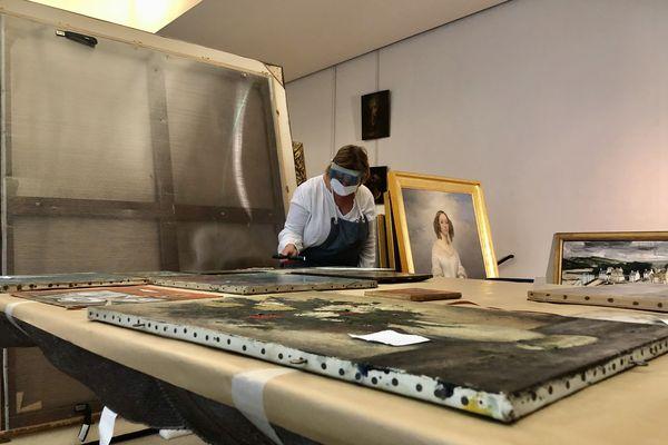 Dans l'atelier de restauration du Musée des Beaux Arts de Rouen, trois restauratrices remettent en état de présentation les peintures.