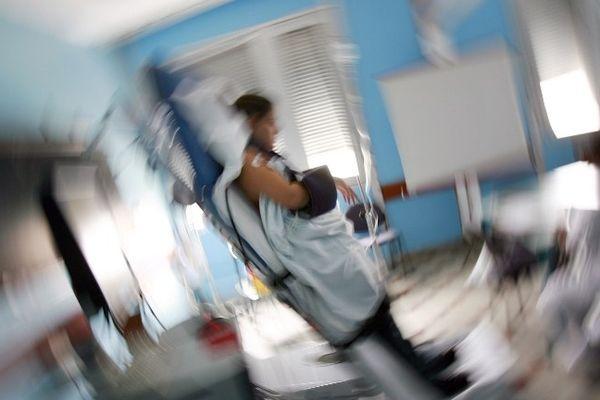 """Une personne soumise au """"tilt-test"""", lit inclinable relié à un ordinateur qui mesure divers paramètres (rythme cardiaque, tension artérielle...) - illustration"""