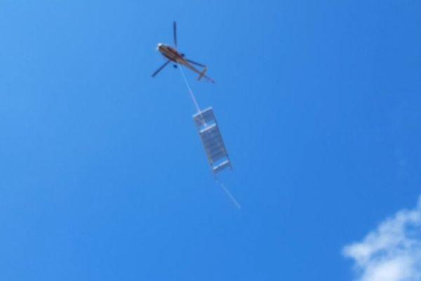 Une partie de la nouvelle passerelle métallique transportée par hélicoptère