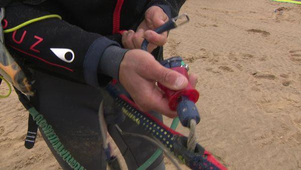 Un moniteur de kitesurf réalise une démonstration avec le matériel de sécurité qui permet selon lui d'éviter les accidents.