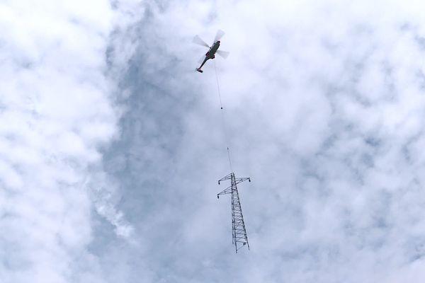 Un hélicoptère est utilisé sur ce chantier de remplacement de pylônes électriques.