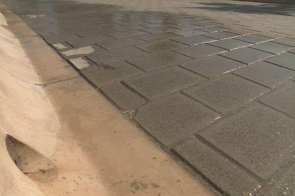 La fabrication des pavés en coquillage et l'aspersion d'eau permettent de faire baisser la température au sol.
