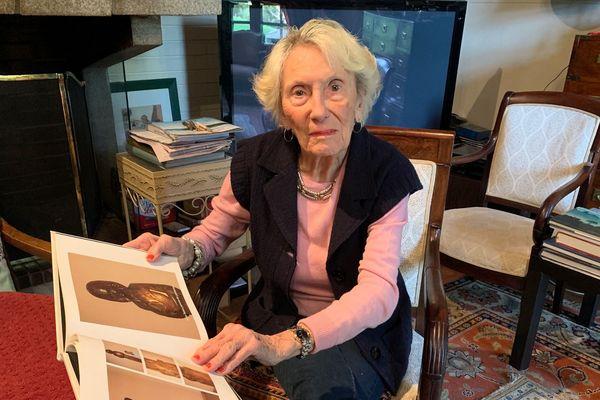 Noëlle Bennett avec un livre représentant la Sainte-Geneviève d'Anna Quinquaud.