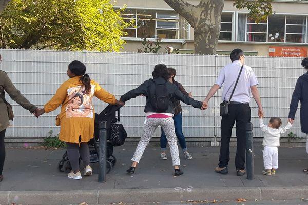Des parents de Saint-Denis forment une chaîne humaine devant une école de Saint-Denis, début septembre.