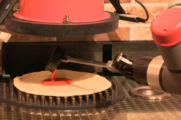 Le robot pizzaïolo de la pizzeria Pazzi, étalant de la sauce tomate sur une pâte, à Paris.