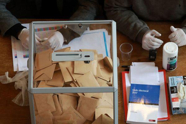Des assesseurs portant des gants lors du premier tour des élections municipales le 28 mars 2020.