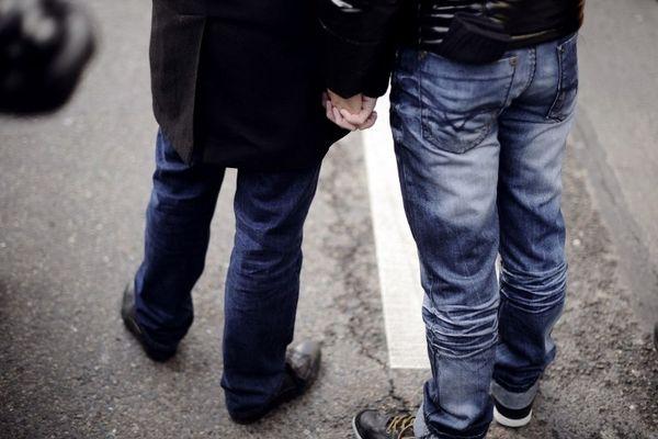 Deux hommes se tiennent la main lors de la manifestation du 16 décembre à Paris.
