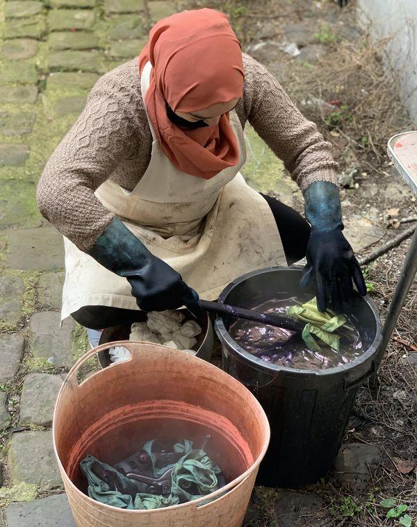 Une salariée de Mode Estime en train de teindre des sacs avec de l'indigo. Crédit Mode Estime.