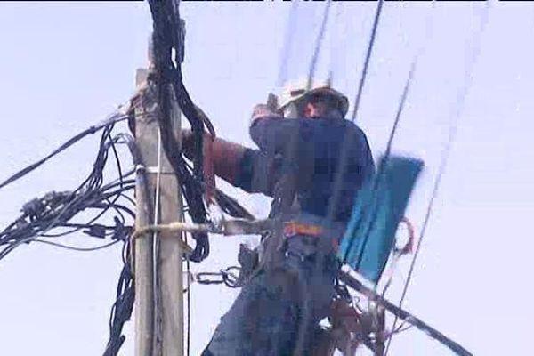 Illustration/ Un anget d'EDF intervient sur une ligne électrique après une tempête, en 2019.