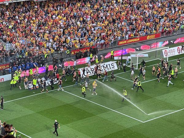 Des supporters lensois sur la pelouse du stade Bollaert-Delelis lors de la mi-temps, samedi 18 septembre 2021.