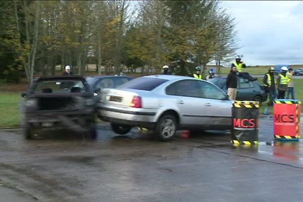 La voiture grise, bloquée par la noire, effectue une marche arrière violente pour se dégager.