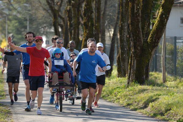 """Des participants à l'ASPARUN accompagnent un enfant assis dans une """"joëlette"""" pour lui permettre de vivre la course"""