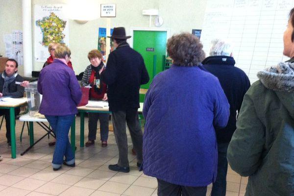 Des électeurs dans un bureau de vote de La Guerche-sur-l'Aubois, dans le Cher, le dimanche 29 mars 2015.