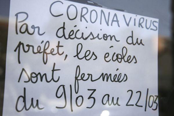 Une affiche à l'entrée d'une école annonçait la fermeture des classes pour une première quinzaine.