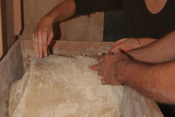 Julie et Bernard pétrissent la pâte à la main.