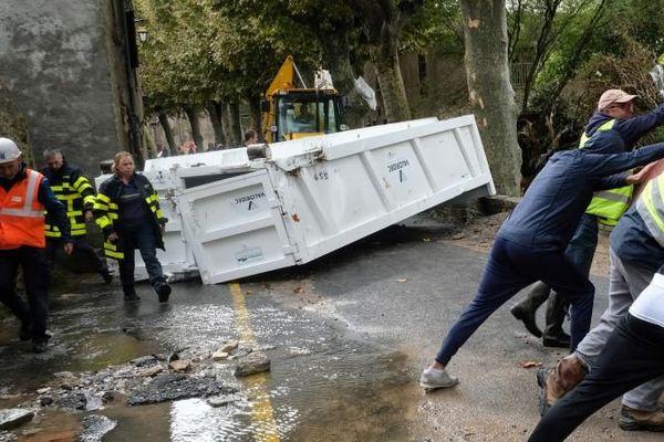 Des habitants de Villegailhenc (Aude) retournent une voiture endommagée par les inondations, le 15 octobre 2018.