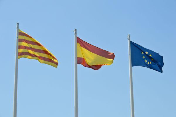 A gauche, le drapeau officiel de la région de Catalogne flottant aux côtés des drapeaux espagnol et européen.