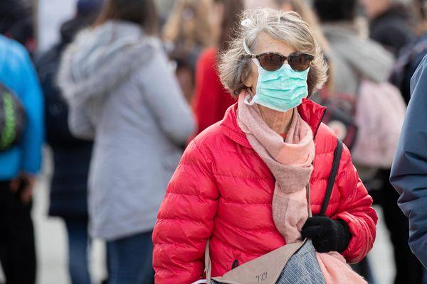 Une passante portant un masque devant le Louvres, à Paris - Photo d'illustration