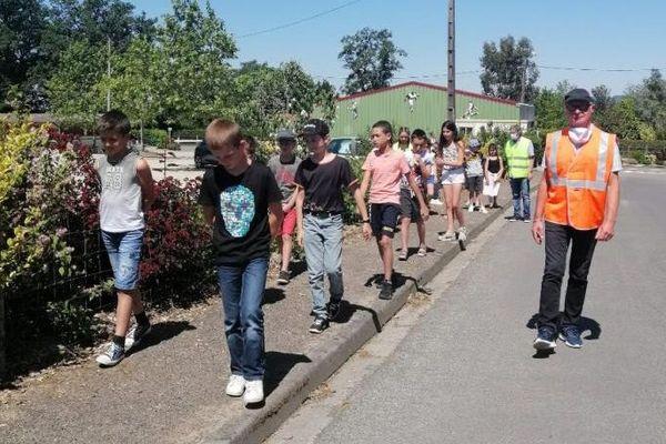 Monsieur le maire de Peyrilhac et l'un de ses adjoints encadrant deux groupes d'élèves pour les emmener à la cantine.